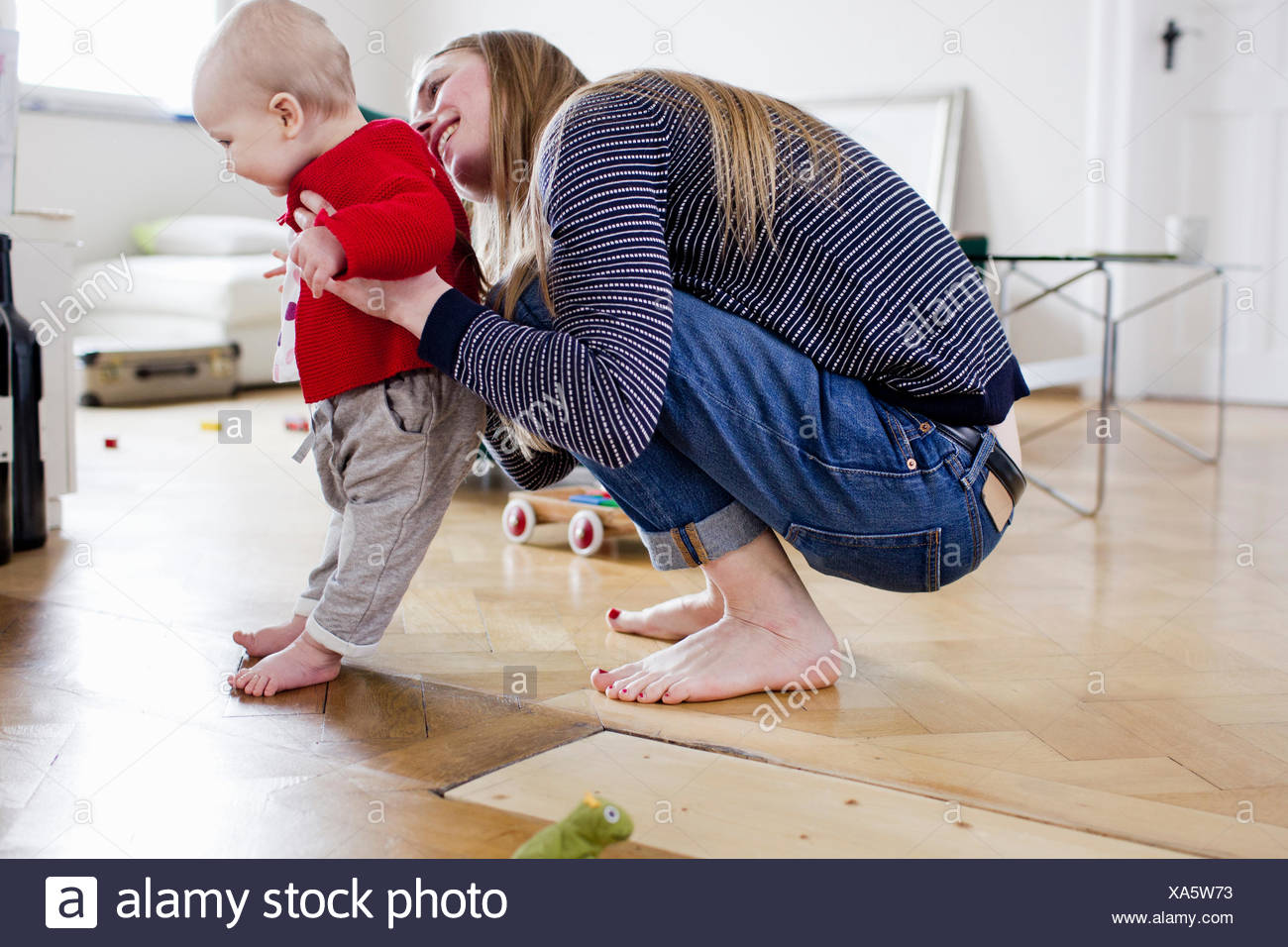 Mid adult woman holding baby daughter to take first steps - Stock Image