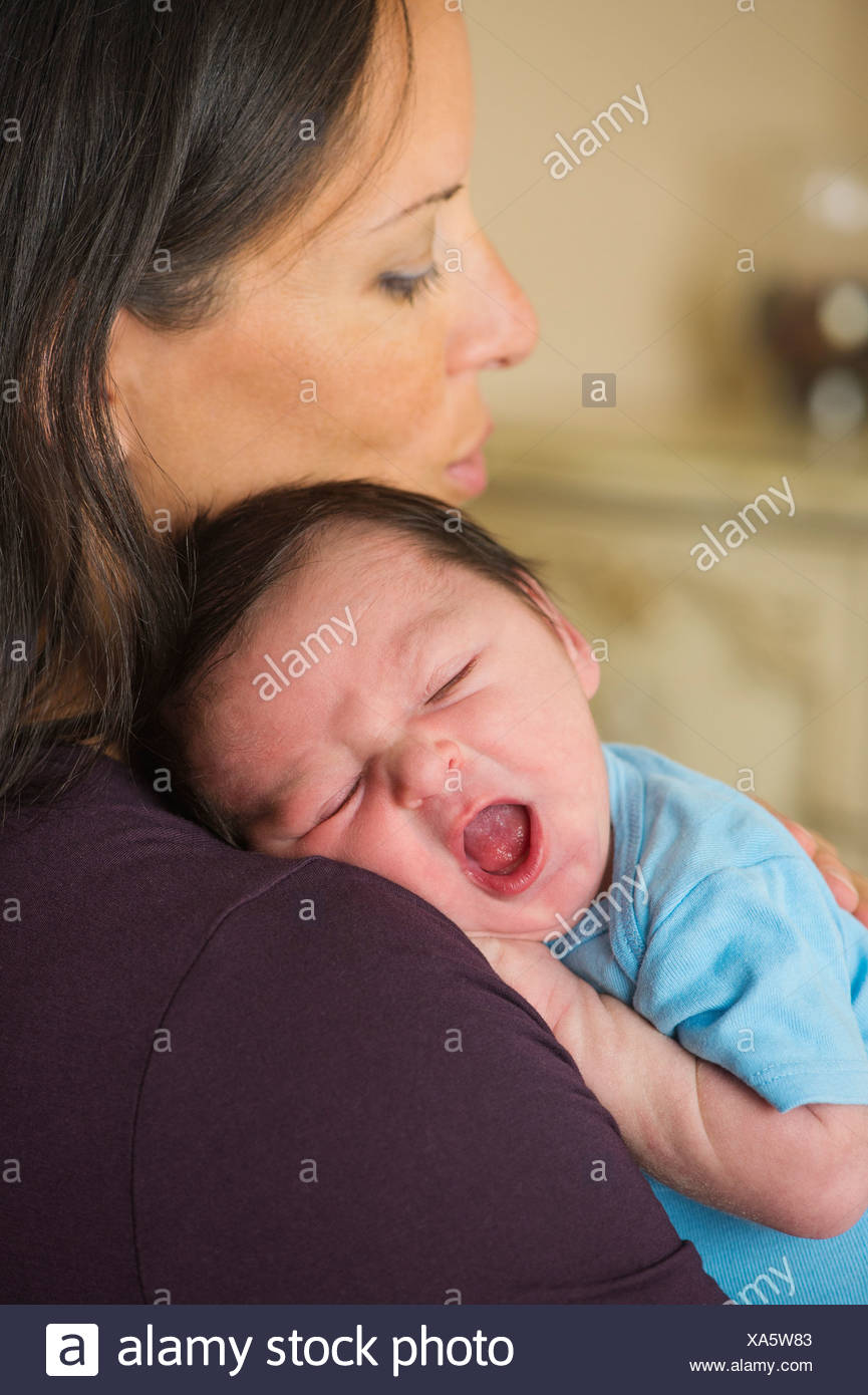 Portrait of mother holding newborn baby (0-11 months) - Stock Image