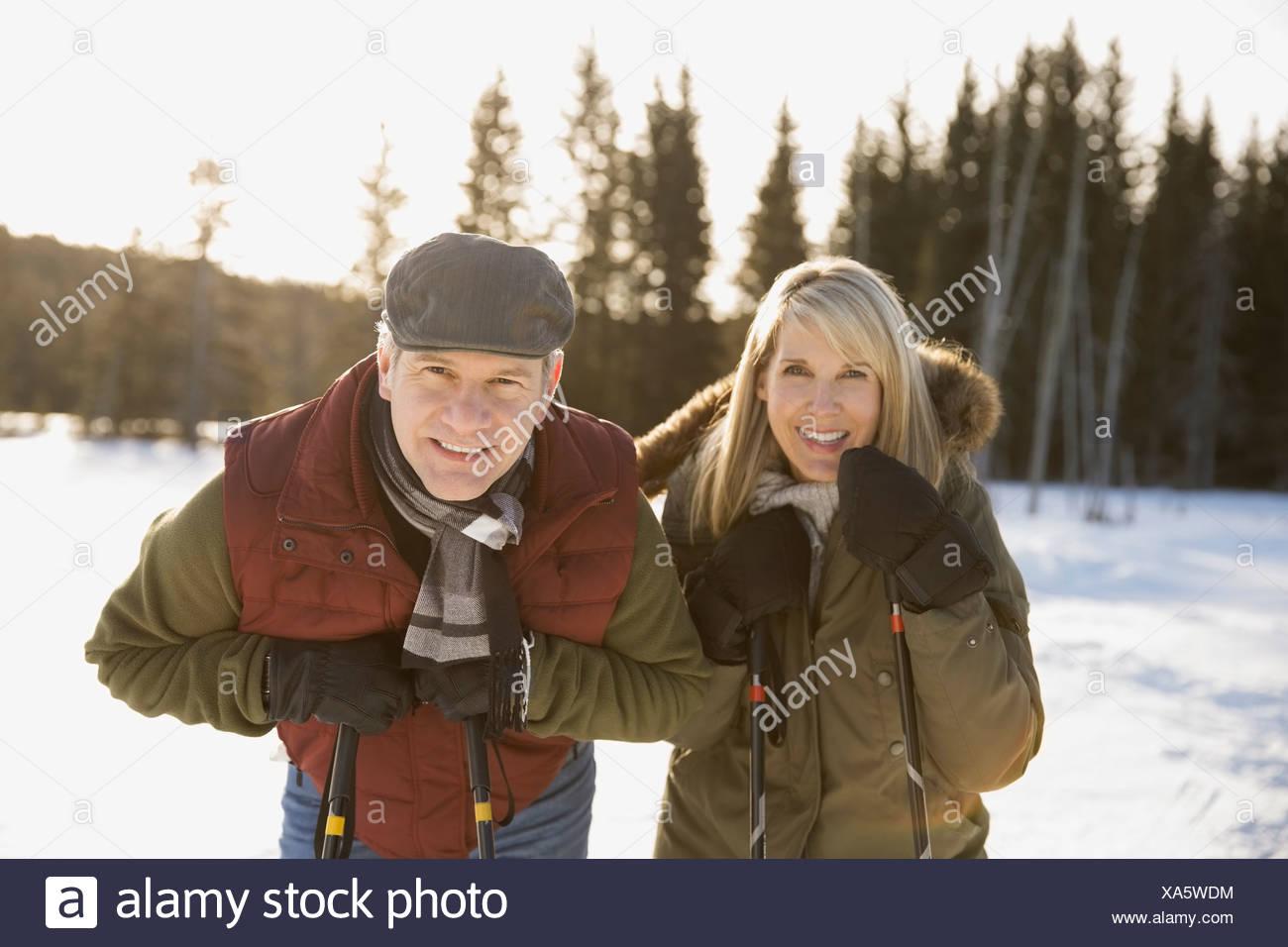 Portrait of smiling couple holding ski poles outdoors - Stock Image