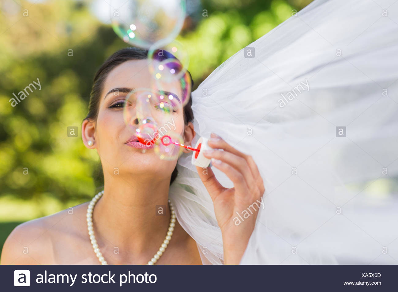 Bride blowing soap bubbles in park - Stock Image