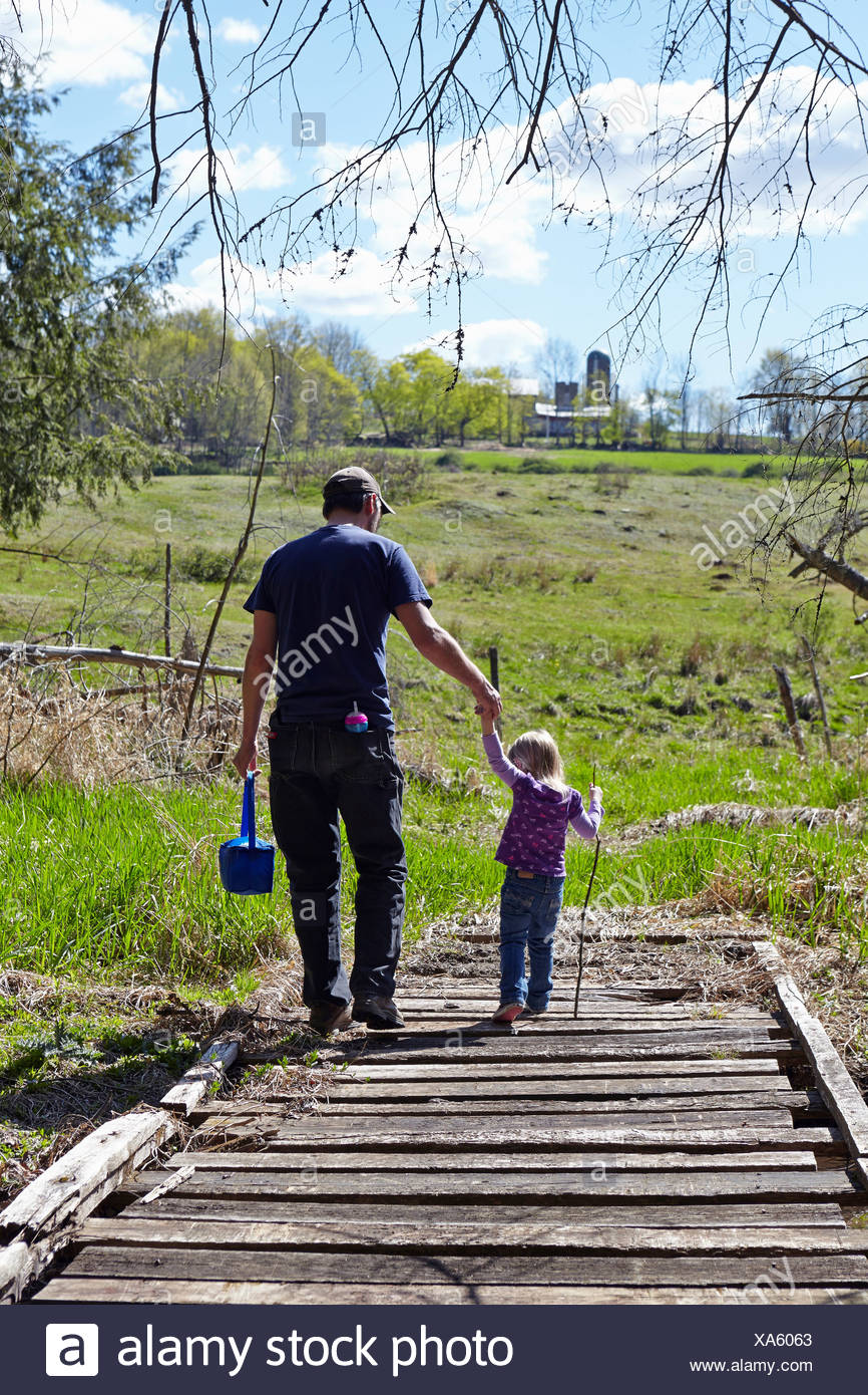 Father and daughter holding hands and walking over wooden bridge - Stock Image
