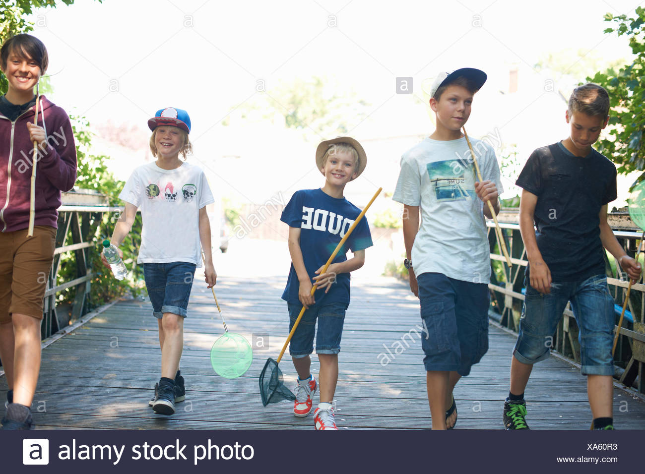 Group of boys on bridge with fishing nets - Stock Image
