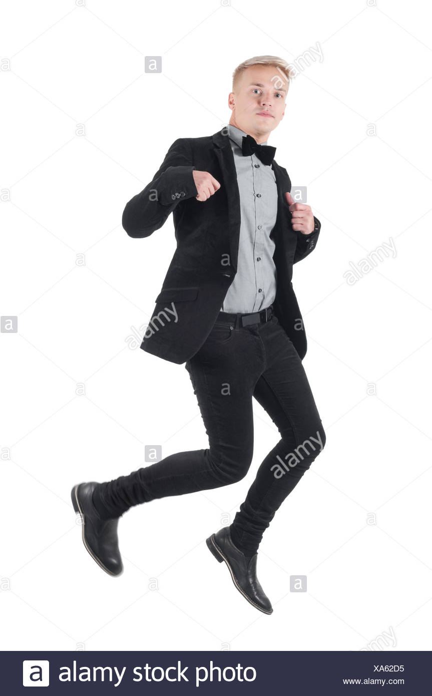 Handsome man in jacket and bow-tie jumping - Stock Image