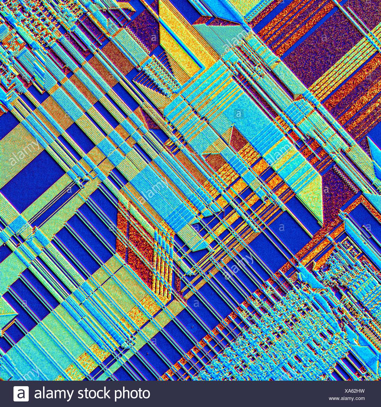 Computer chip. Coloured light micrograph of the surface of an integrated chip from a computer. This integrated circuit has been made by imprinting microscopic electronic components onto the surface of a wafer of silicon. Integrated circuits can be made mu - Stock Image