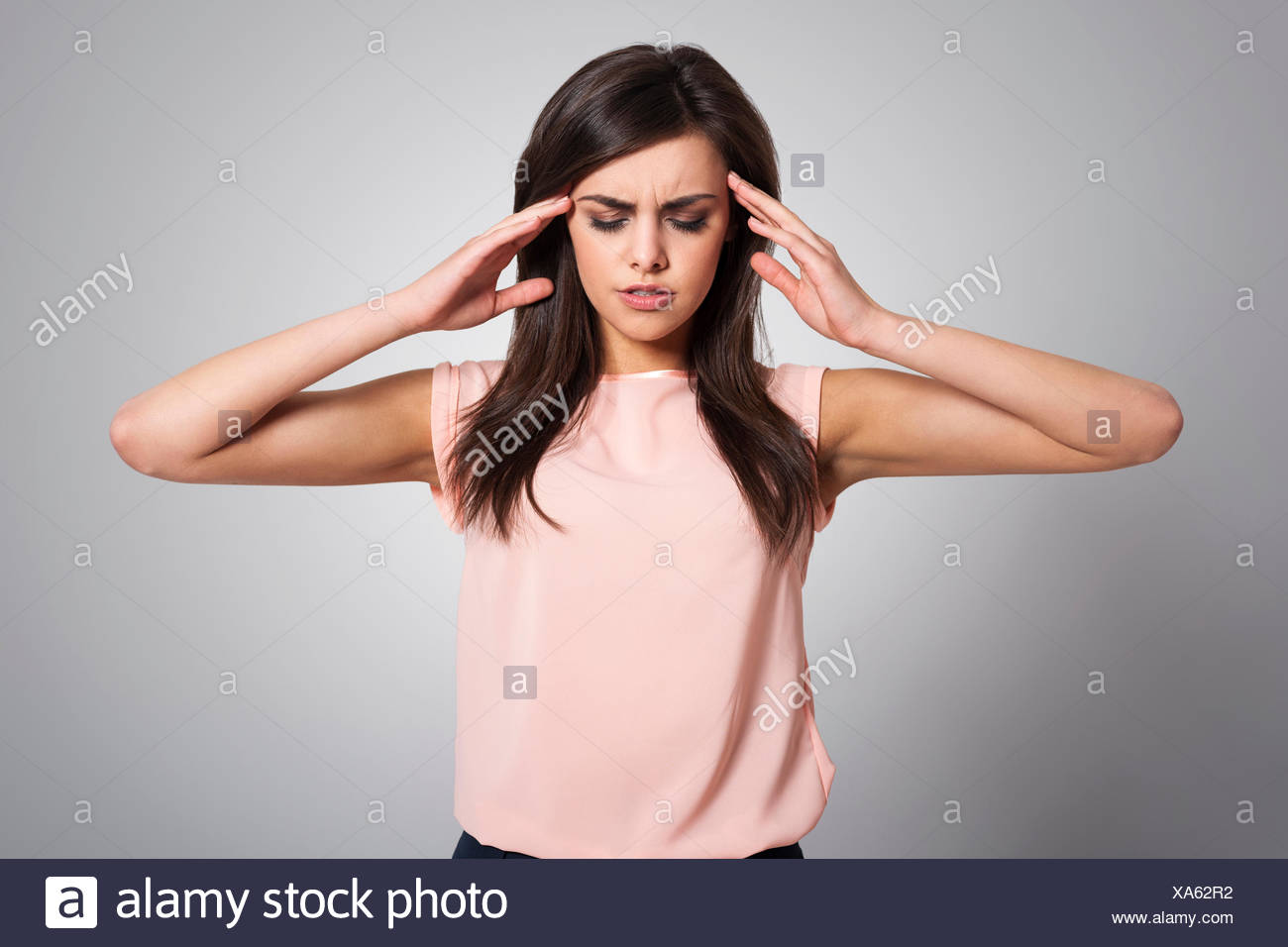 Woman with a migraine massaging her temples. Debica, Poland - Stock Image