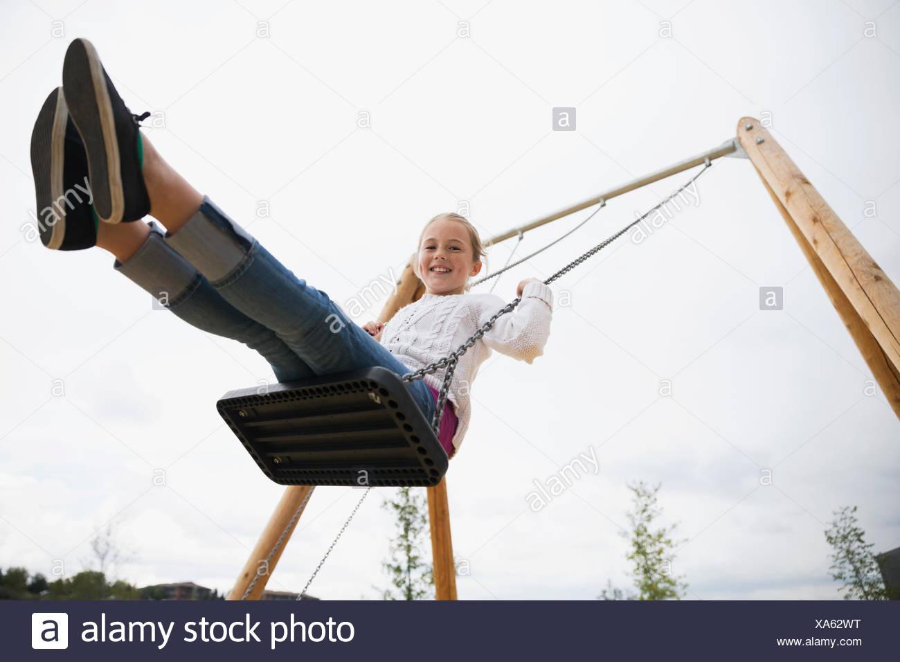 Portrait smiling girl swinging at playground - Stock Image