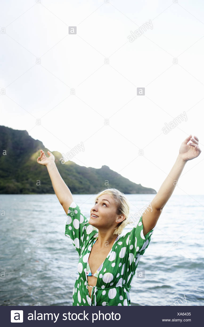 Young woman with arms raised - Stock Image