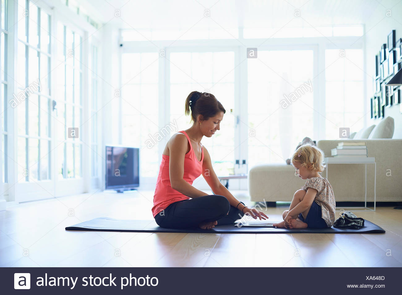Mid adult mother and toddler daughter practicing yoga in living room - Stock Image