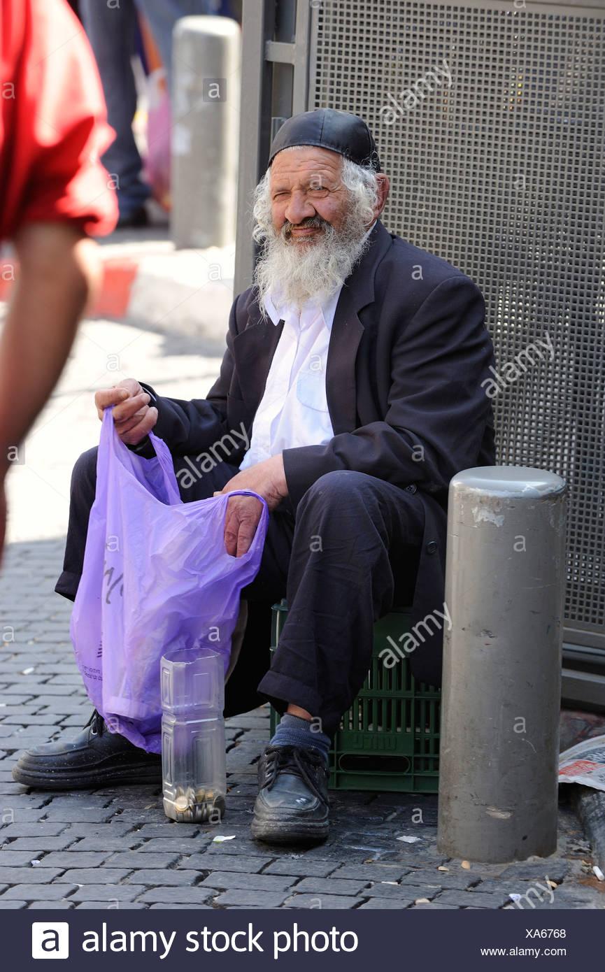 Jewish beggar sitting in front of the Jewish Mahane Yehuda Market, Jerusalem, Israel, Middle East, Southwest Asia - Stock Image