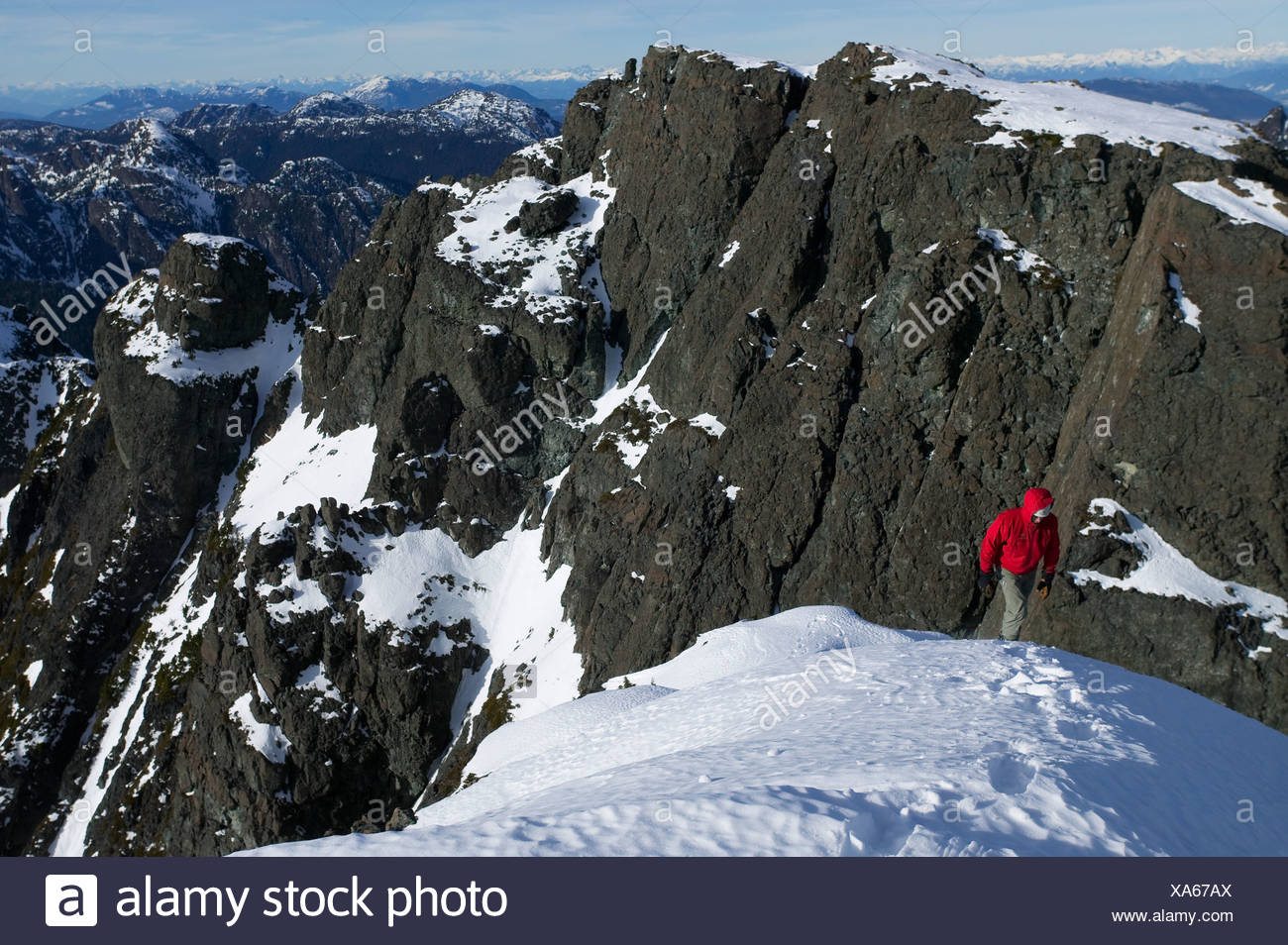 Lone climber ascends to summit snowfield of Mt. Cain looking South towards Campbell River on central Vancouver Island.  British - Stock Image