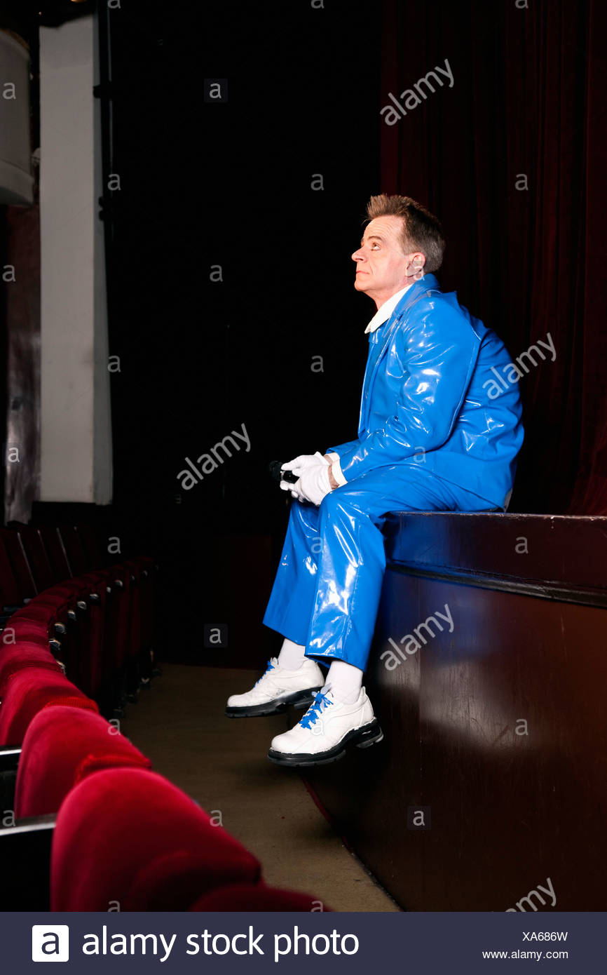 comedian sitting on stage - Stock Image