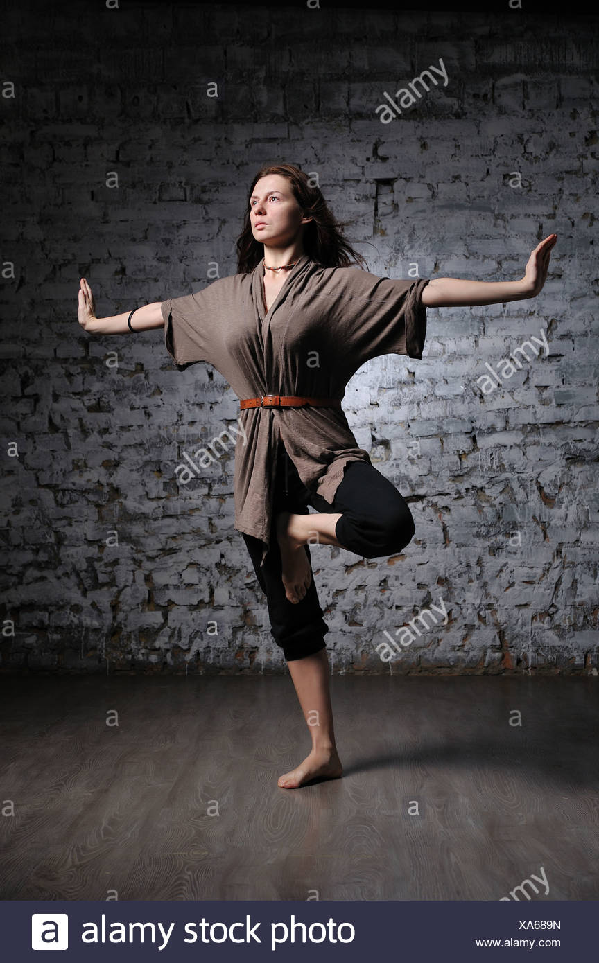 Full-length portrait of young beautiful woman doing yoga excercise against a brick wall - Stock Image
