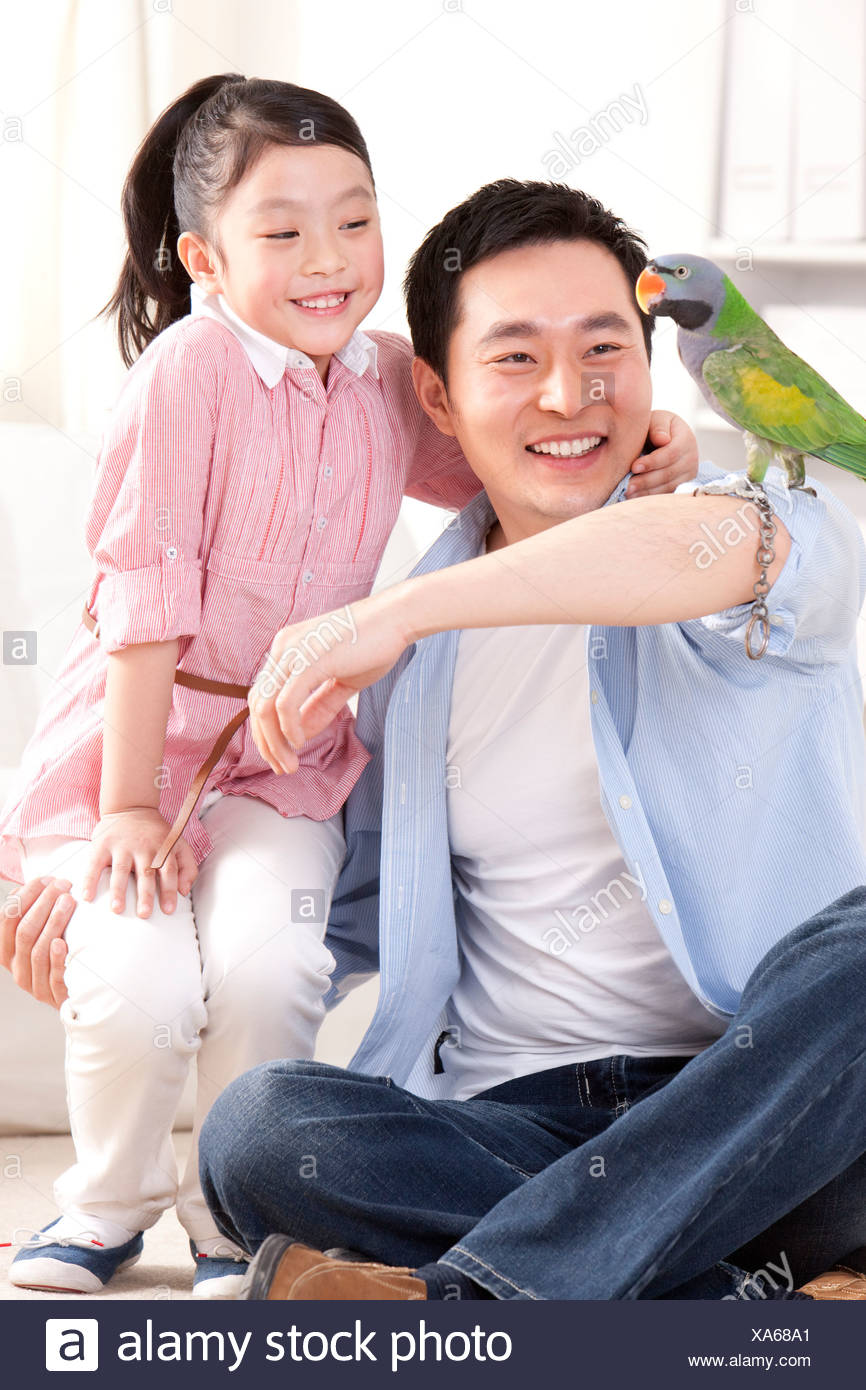 Father and daughter playing with a pet parrot - Stock Image
