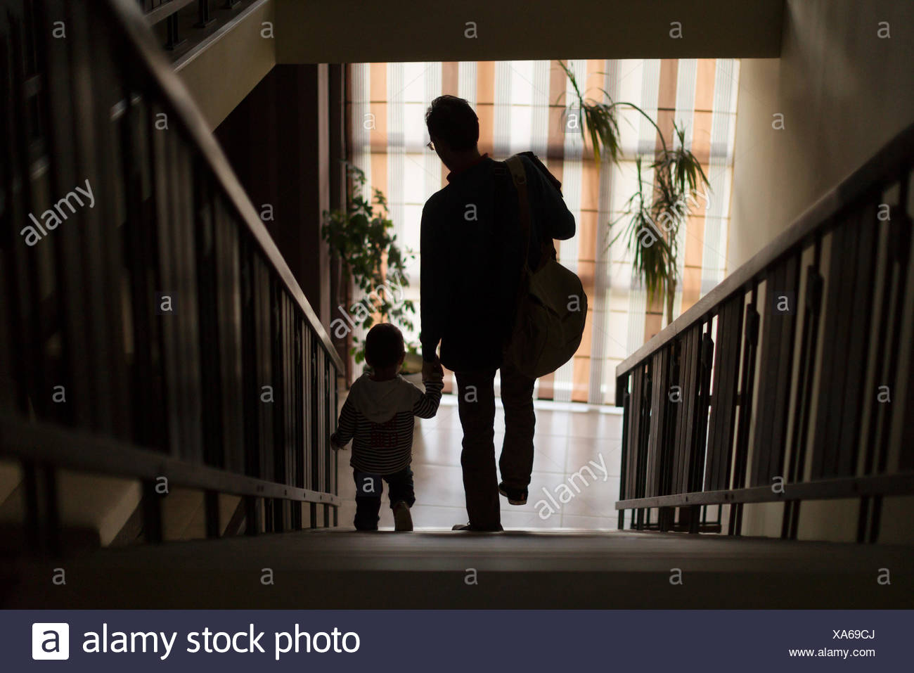 Father and son walking down stairs holding hands Stock Photo