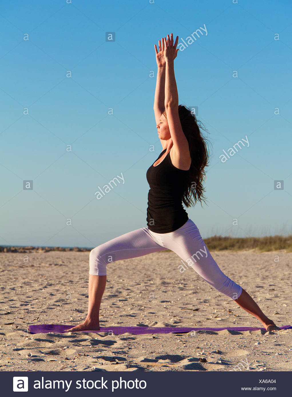 Woman practising warrior 1 yoga pose on beach - Stock Image