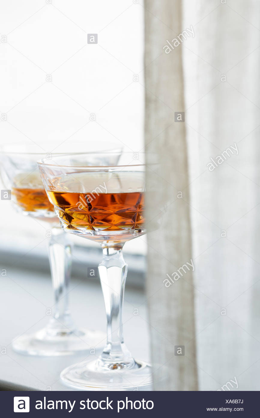 Brandy glasses on a window ledge - Stock Image