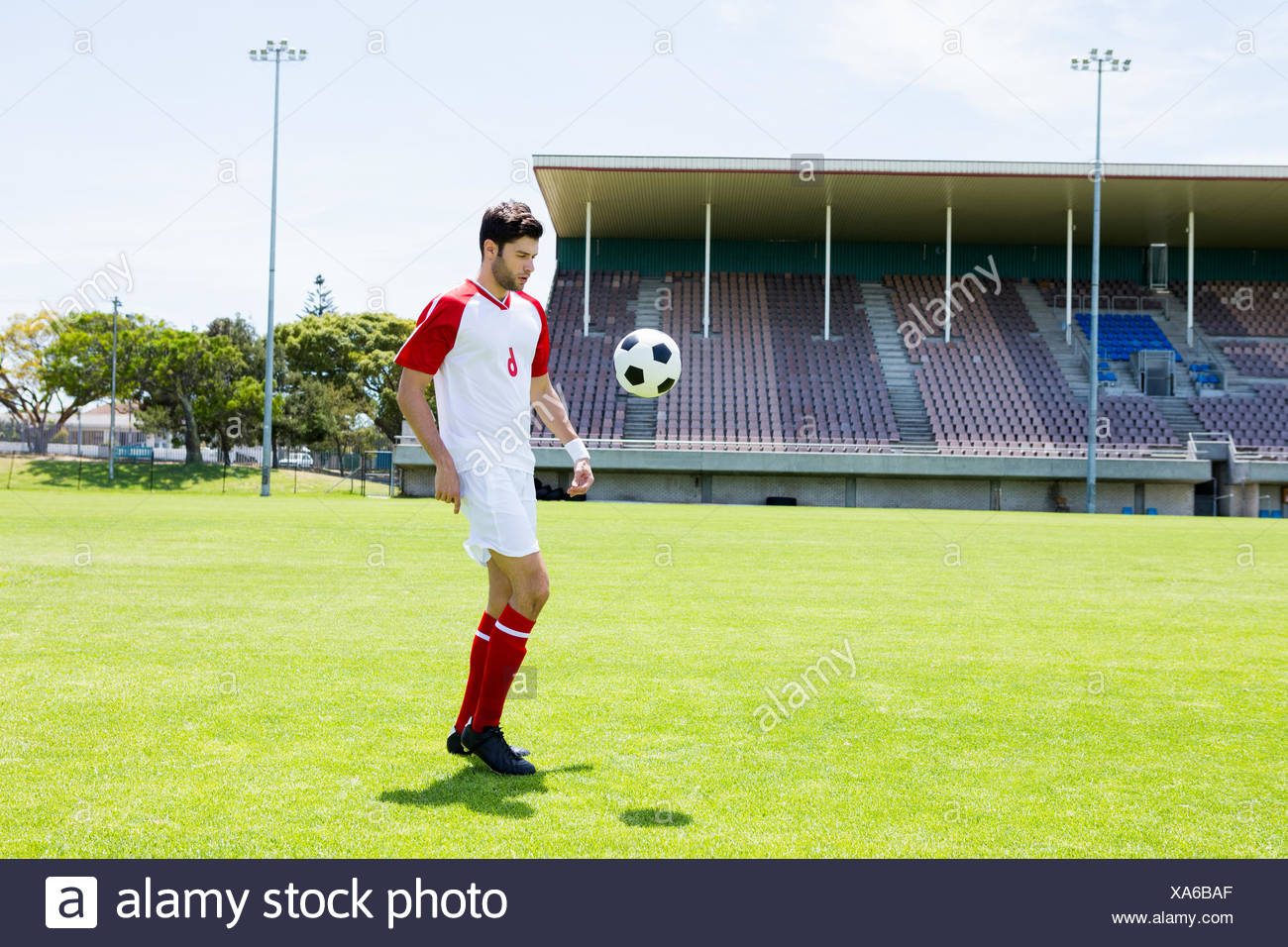 Football player juggling the football with his feet - Stock Image