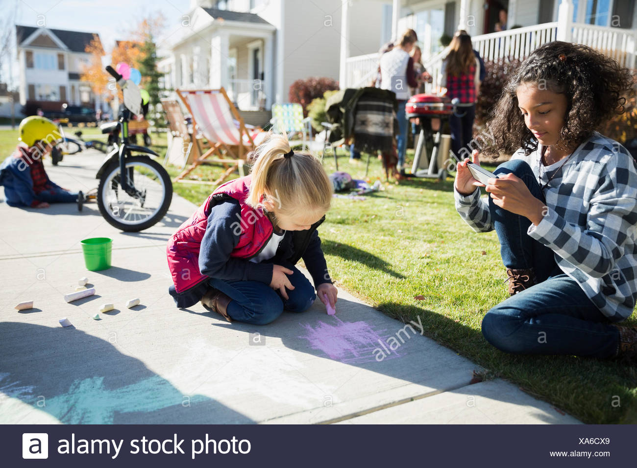Kids drawing on sidewalk with chalk Stock Photo