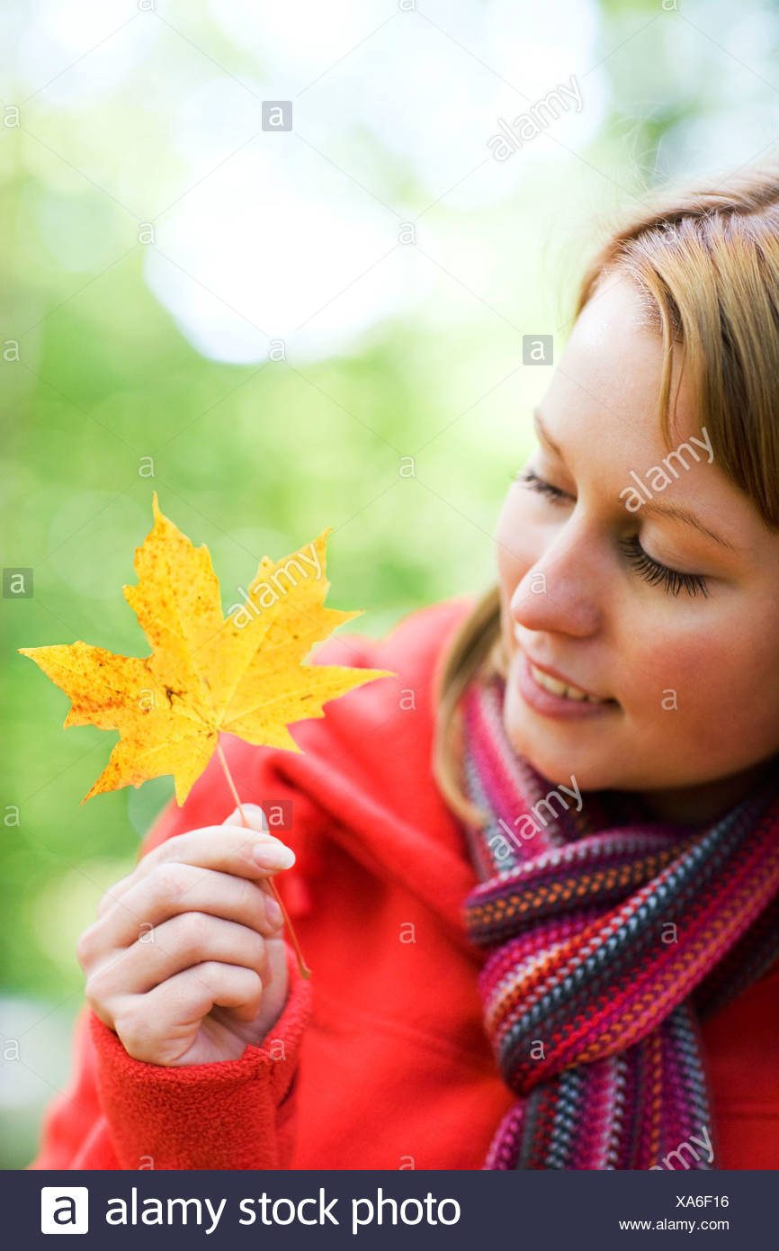 Portrait of a woman holding a maple leaf - Stock Image