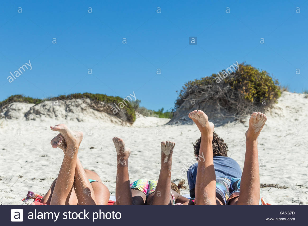 Three children lying on the beach with their legs in the air - Stock Image