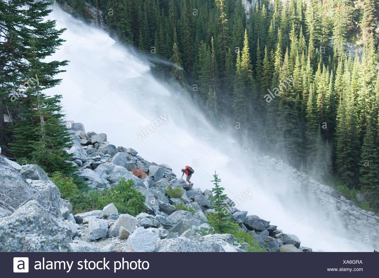 A man hiking next to waterfall, Enchantment Peaks, Alpine Lakes Wilderness, Leavenworth, Washington. - Stock Image