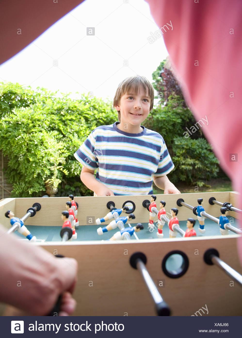 Boy (8-9) playing table football - Stock Image