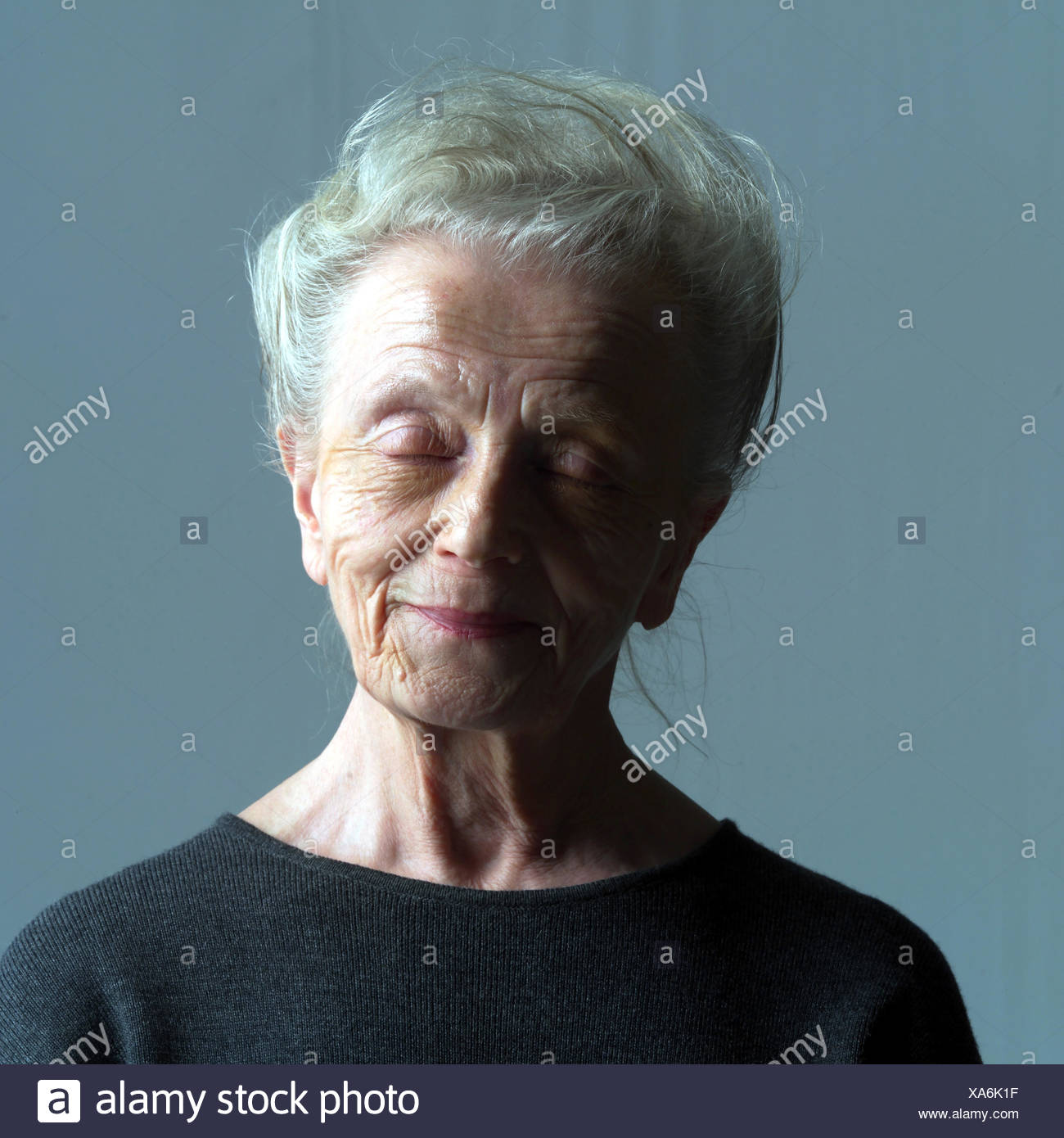 Senior, smile, portrait, model released very closely, studio, pensioner, woman, old, old age, expression, good-natured, good nature, friendly, contently, satisfaction, eyes closed, natural, naturalness - Stock Image