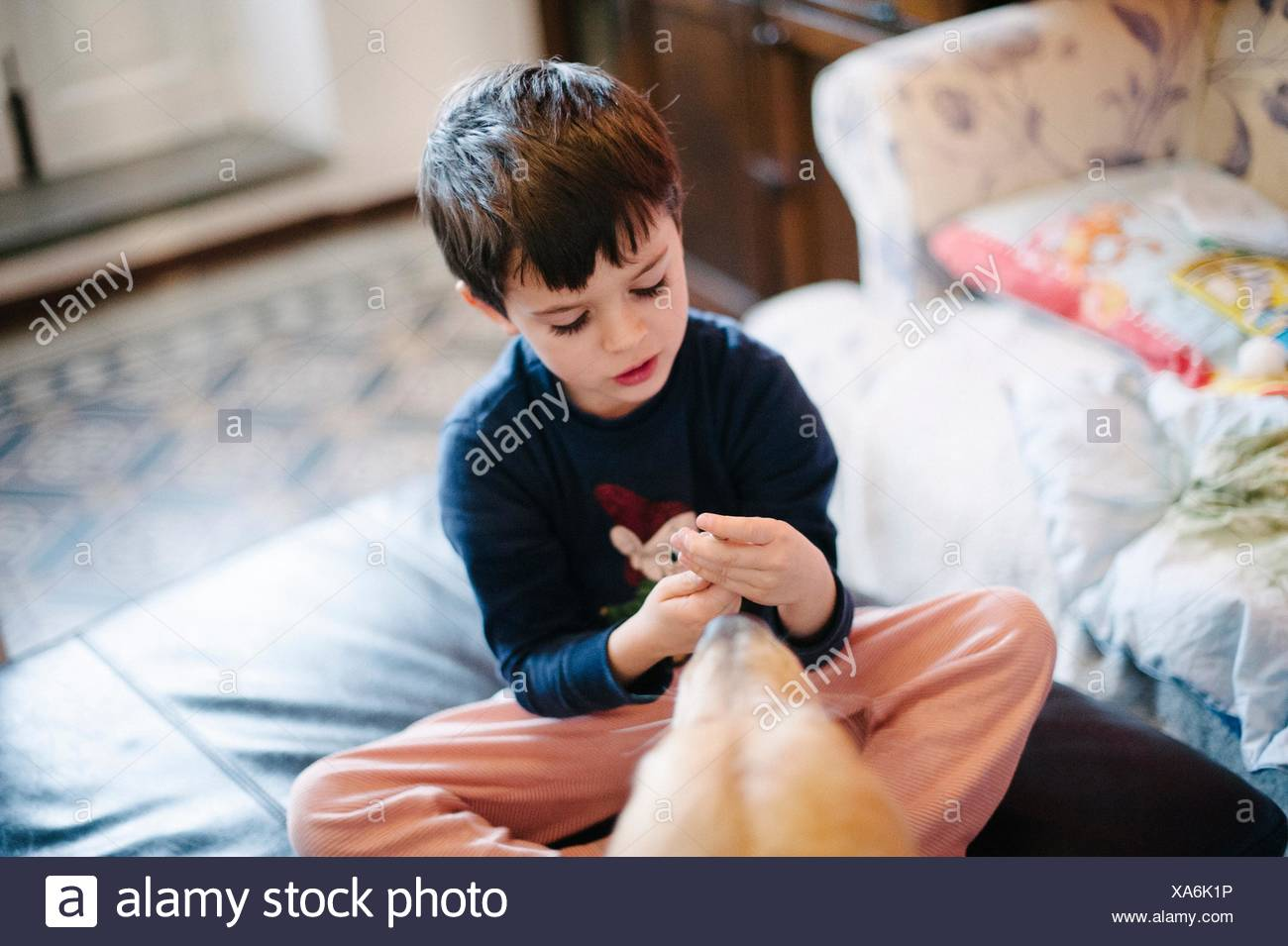 Child plays sitting on poof, dog near - Stock Image