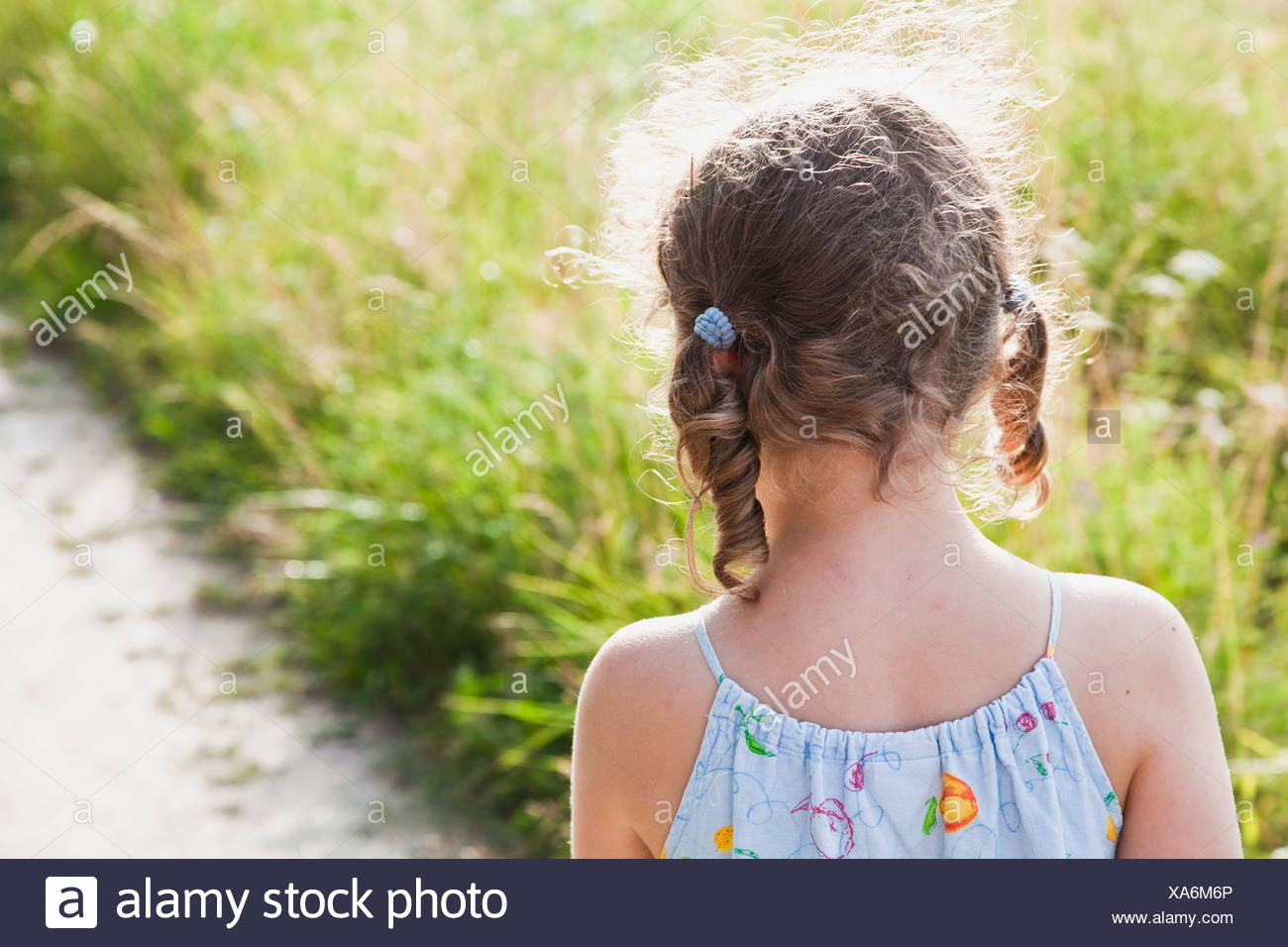 Rear view of girl against grass - Stock Image