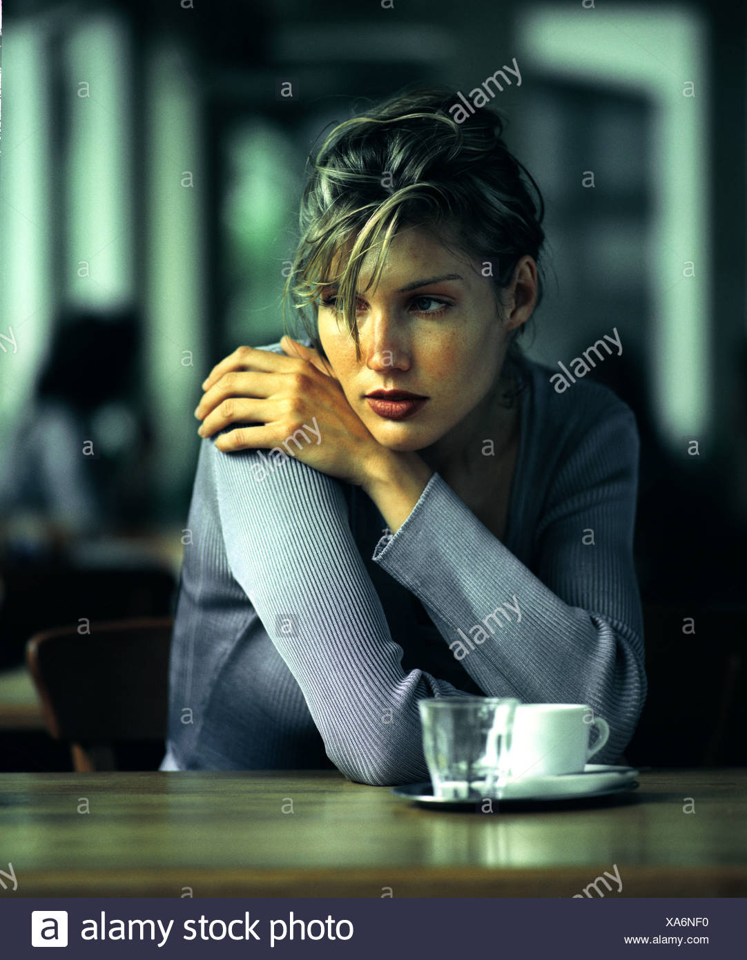 Woman sitting at table - Stock Image