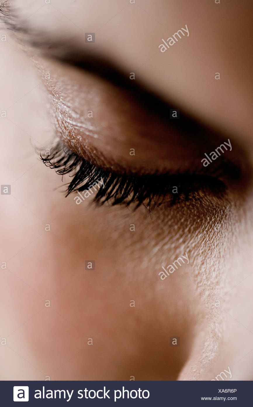 Detail of woman's face showing left eye, looking down - Stock Image
