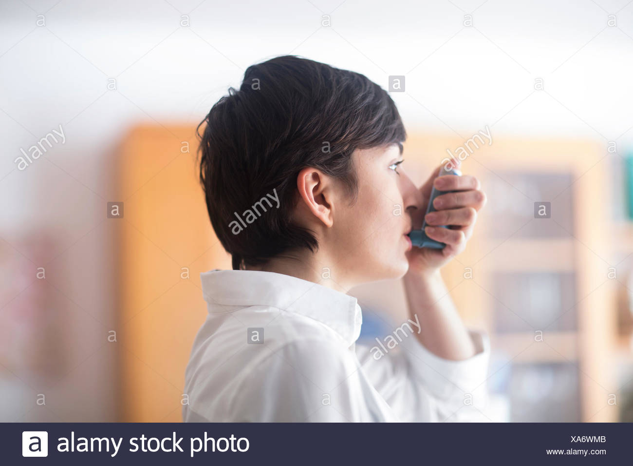 Young woman using inhaler - Stock Image