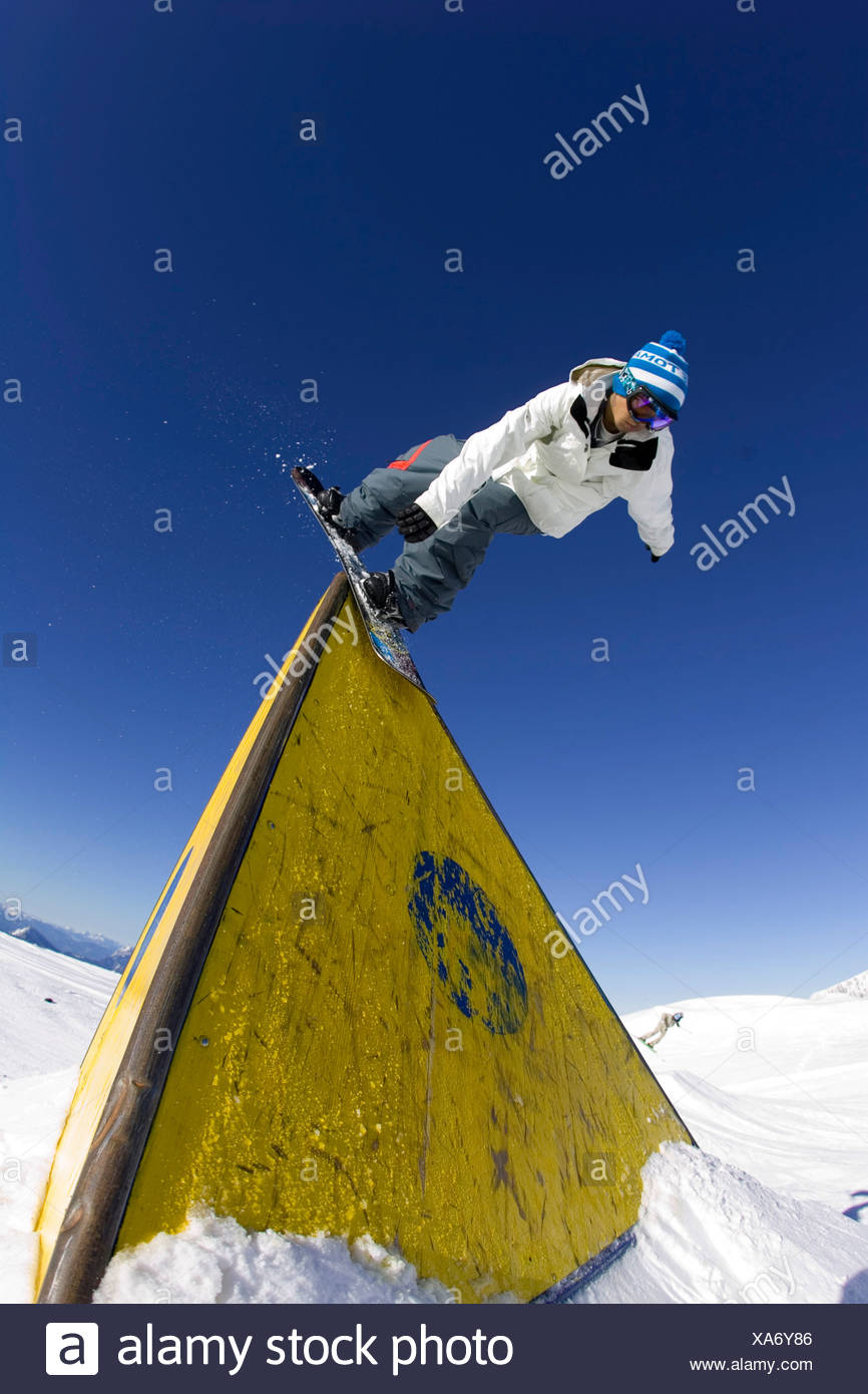 A snowboarder doing a trick at an obstacle, Dachstein, Austria - Stock Image