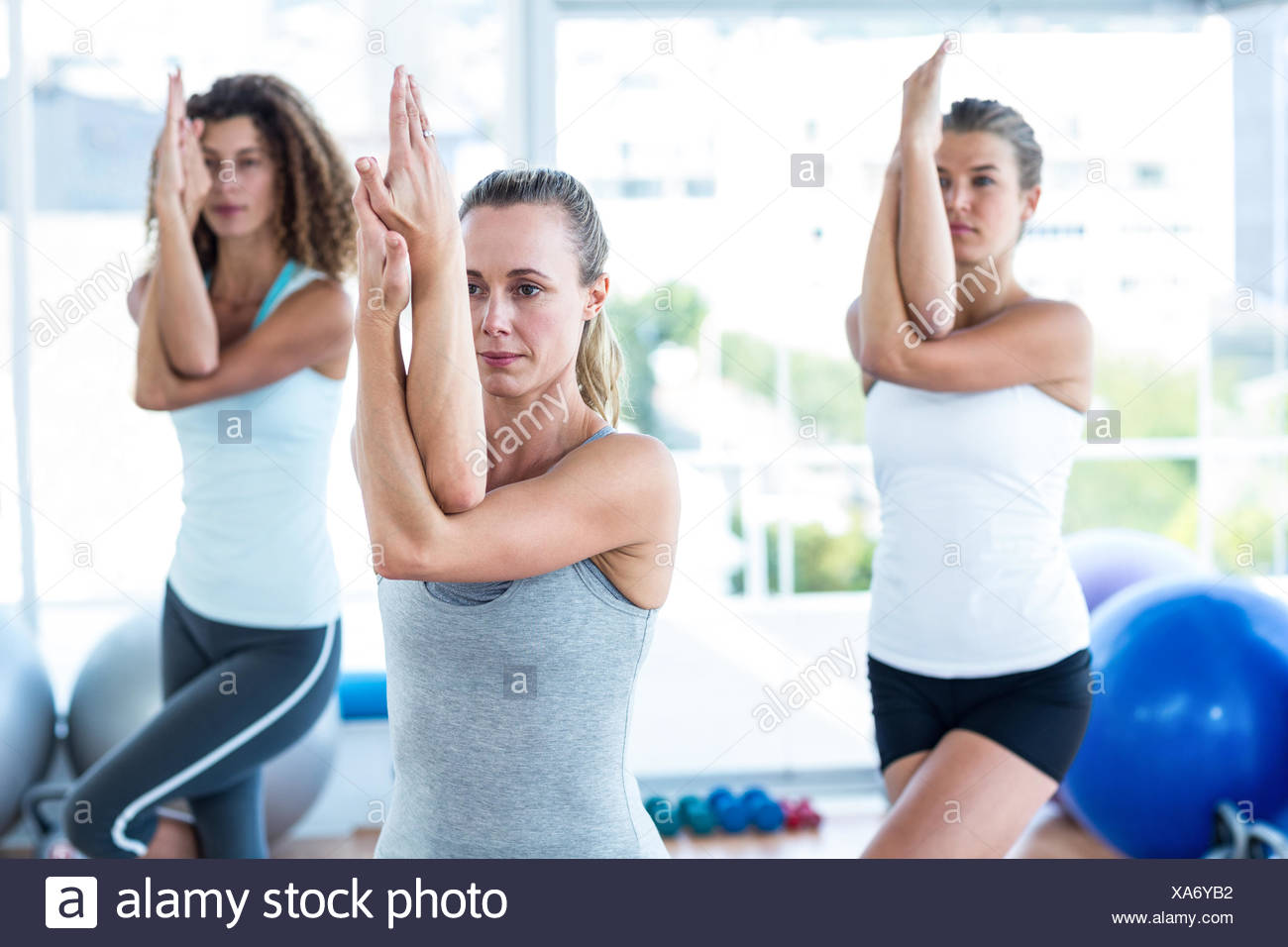 Women doing eagle pose - Stock Image