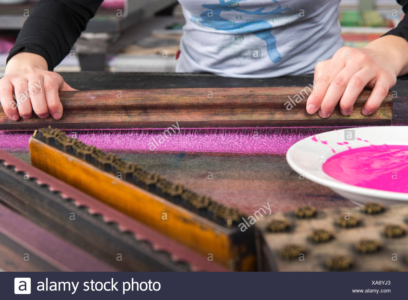 Block printing, hands pressing woodblock on color on felt mat, woodblock and plate with color in front, Bad Aussee, Styria - Stock Image