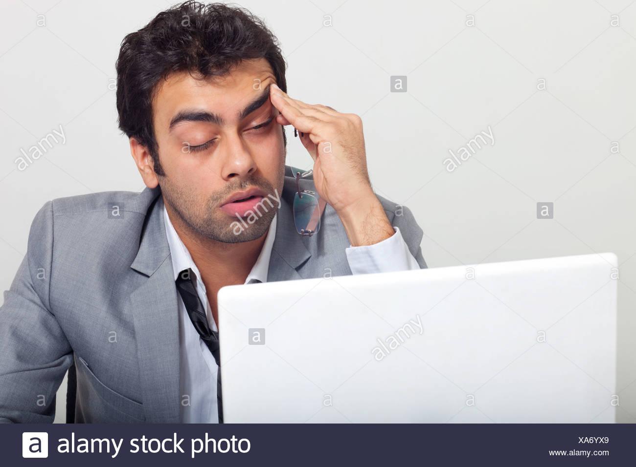 Businessman feeling sleepy at work - Stock Image