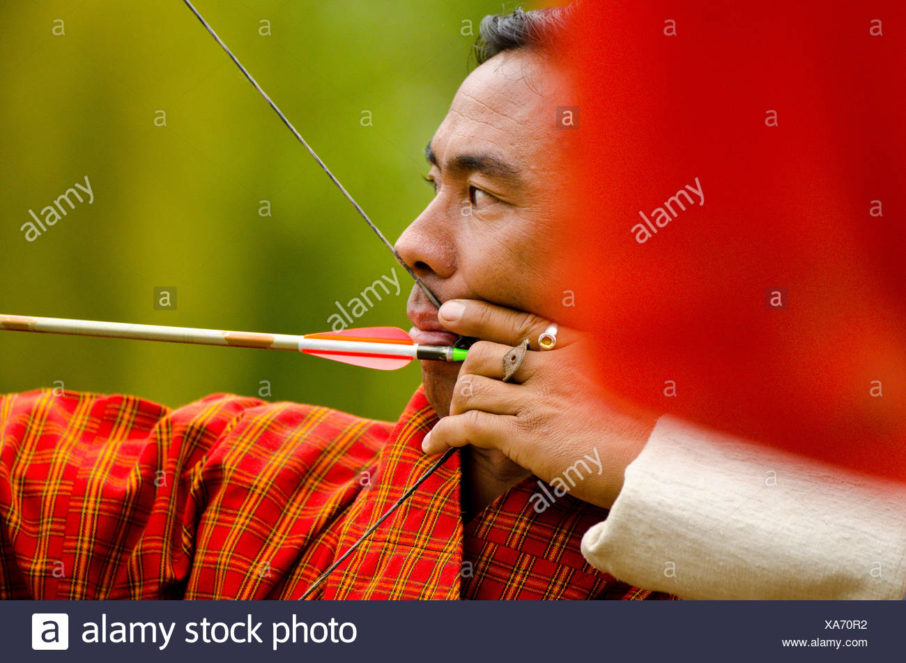 A Buddhist man takes aim with a bow and arrow in Bhutan, where the national sport is archery - Stock Image