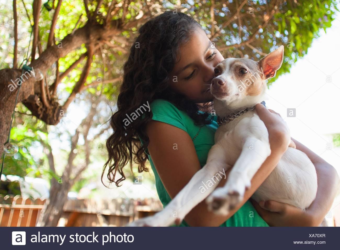 Portrait of girl in garden hugging dog - Stock Image