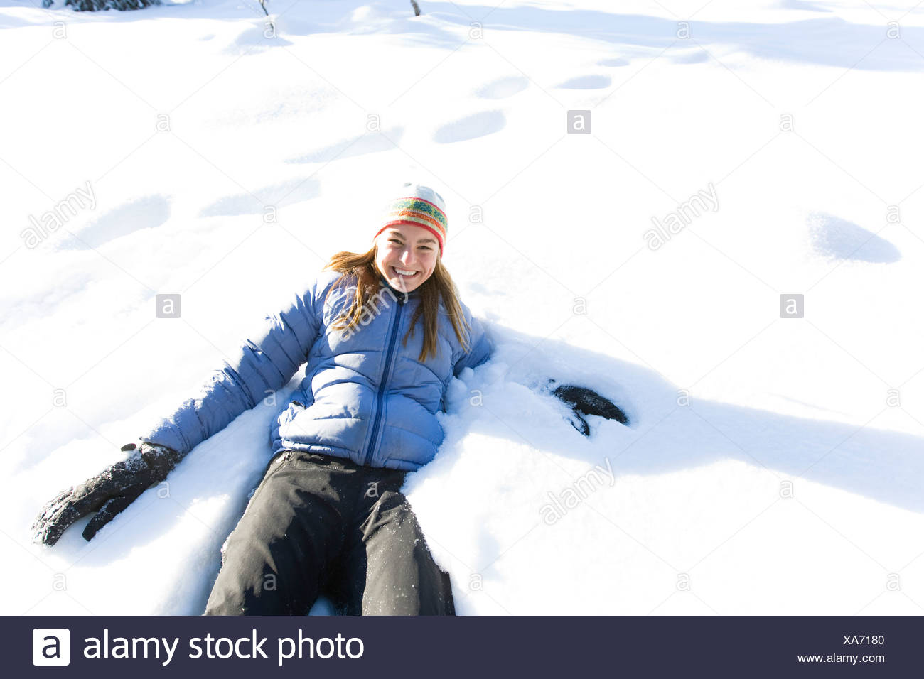 Young woman on snowshoes plays in snow near Homer, Alaska during winter. Stock Photo