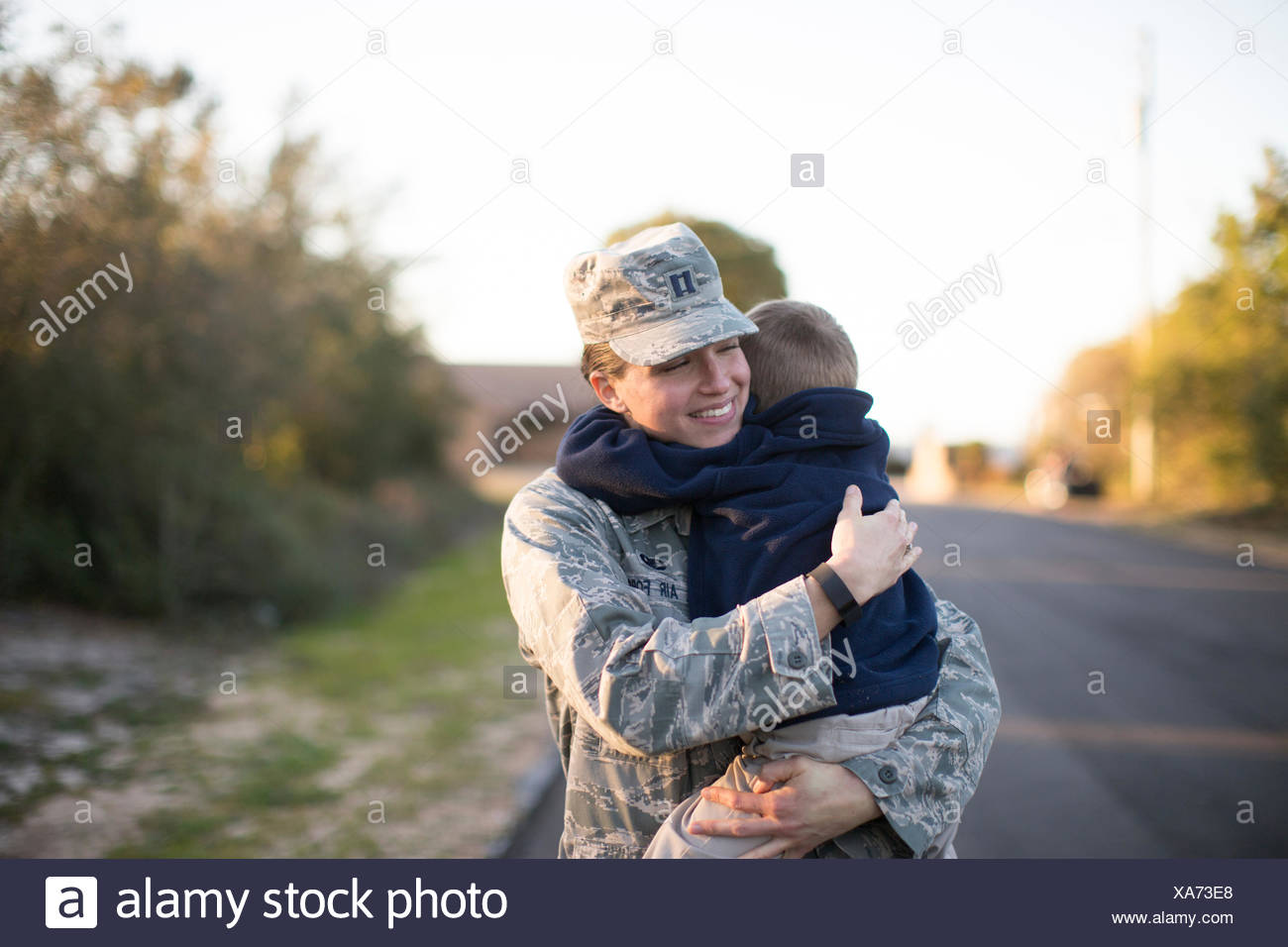 Female soldier hugging son at air force military base - Stock Image