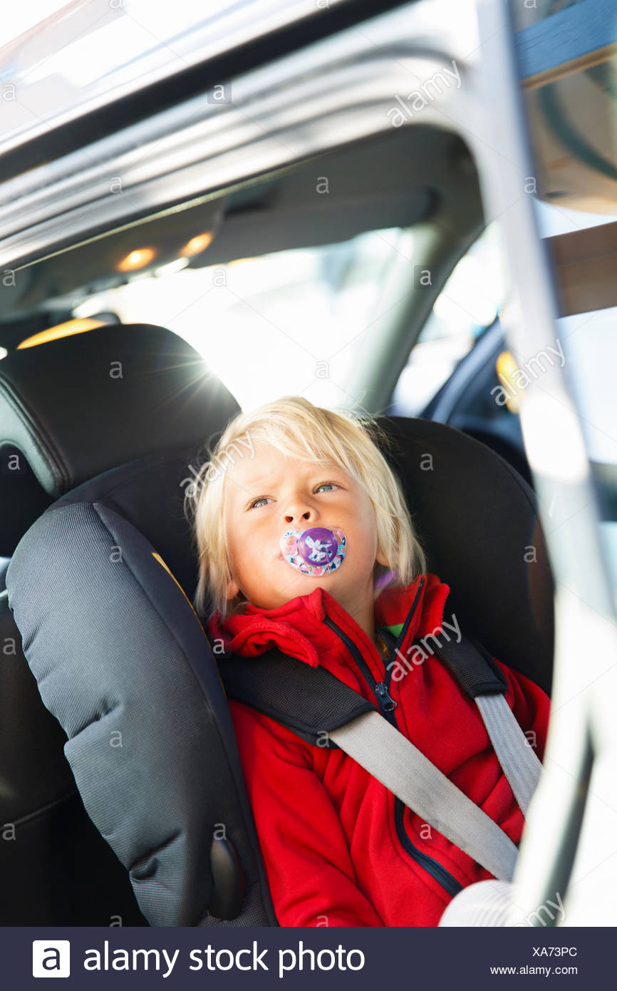 Sweden, Little blonde boy (2-3) fastened to seat in car Stock Photo