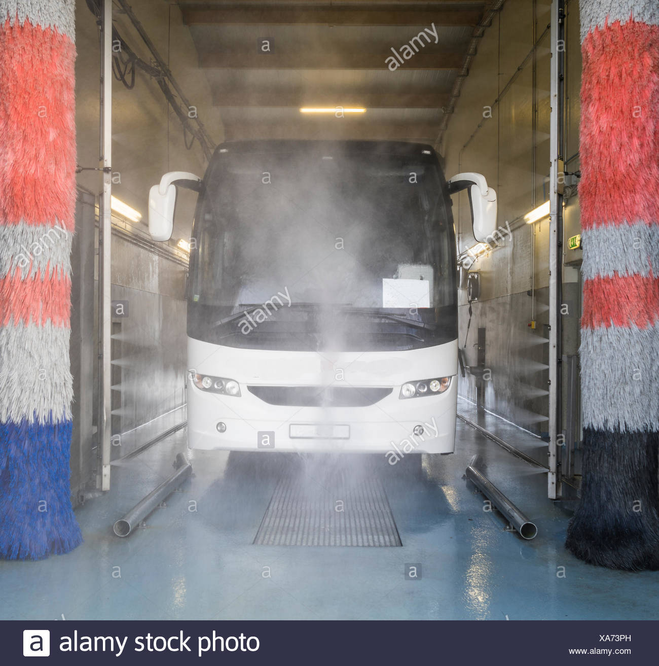Tour bus in a large car wash. - Stock Image