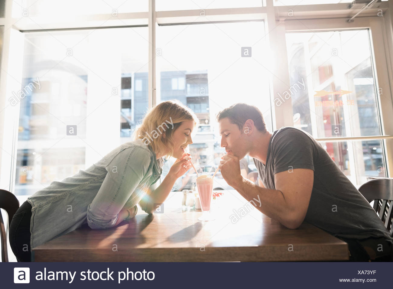 Young couple sharing milkshake at sunny diner table - Stock Image