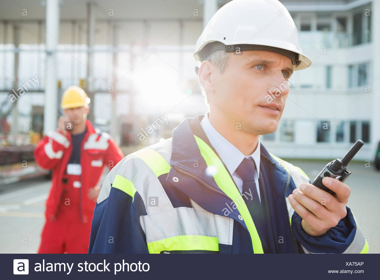 Male worker using walkie-talkie with colleague in background at shipping yard - Stock Image