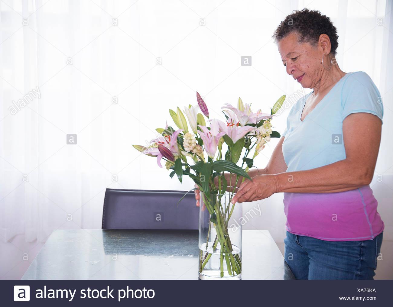 Senior woman arranging vase of flowers Stock Photo