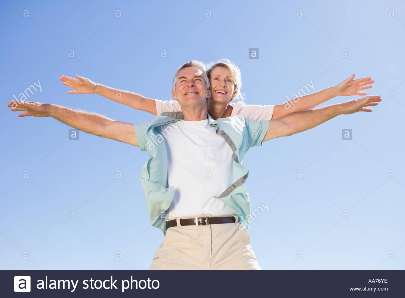 Happy senior man giving his partner a piggy back - Stock Image