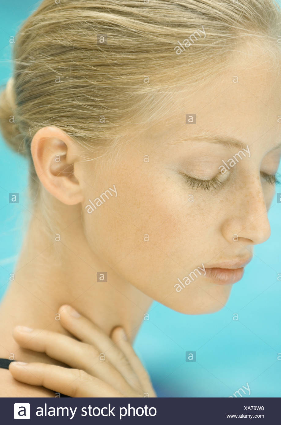 Woman with hand on neck, pool in background - Stock Image