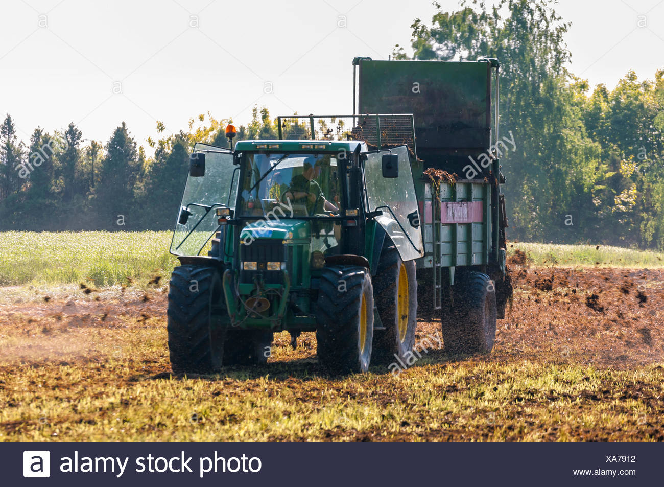 Tractor with manure spreader, farmer working in the fields, spreading manure, Götzenhain, Dreieich, Hesse, Germany - Stock Image