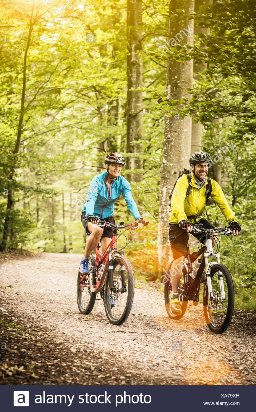 Happy mature mountain biking couple cycling on forest trail - Stock Image