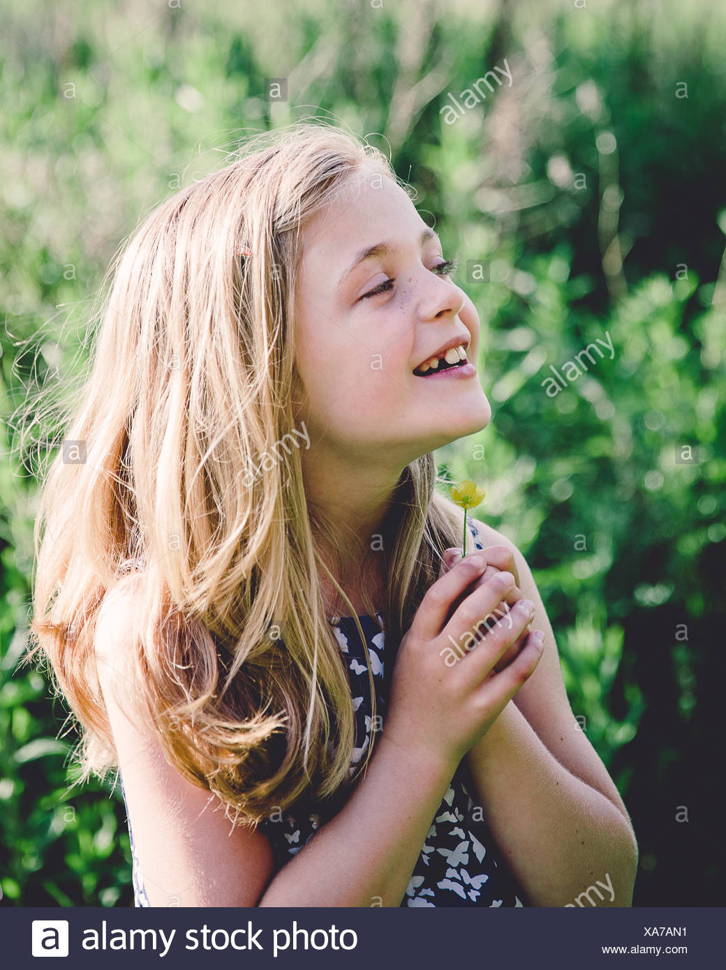 Portrait of a smiling girl holding a buttercup under her chin - Stock Image